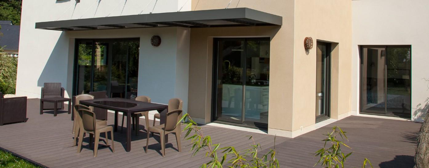 Pergolas au dessus d'une terrasse de maison avec table de salon