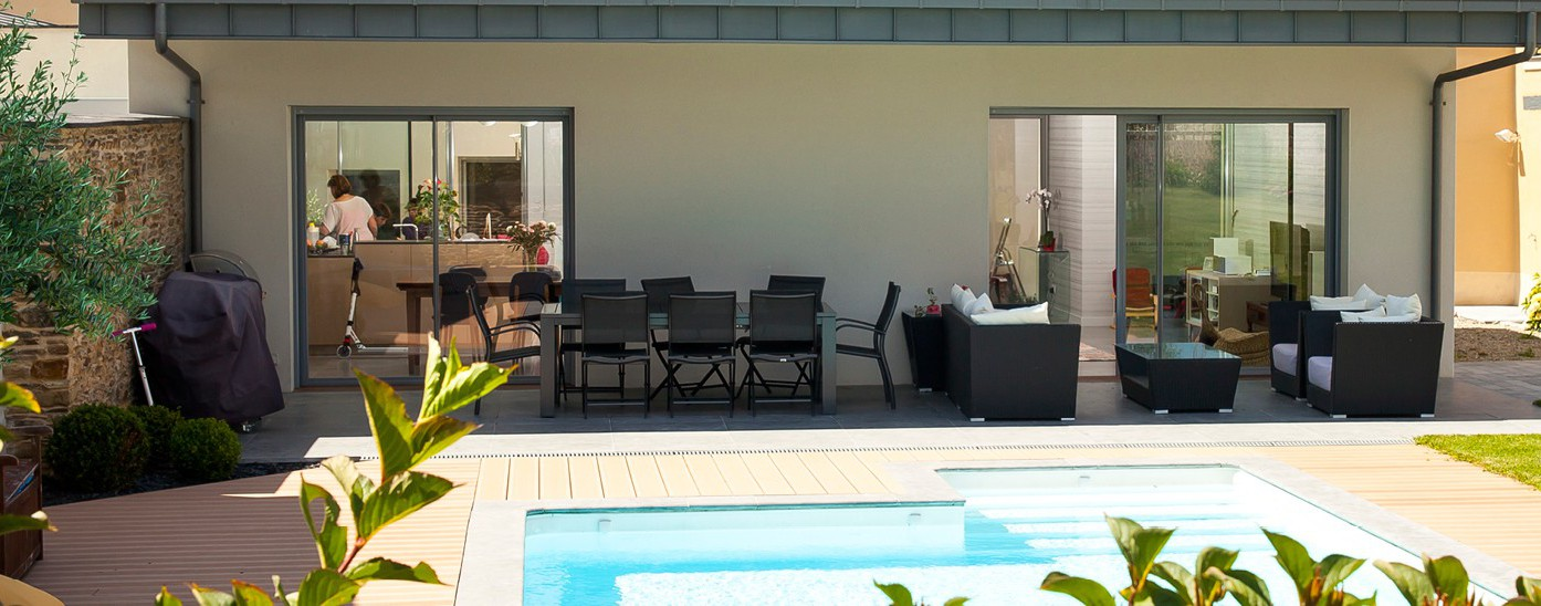 Grandes baies vitrées ouvertes au bord de terrasse et piscine